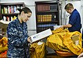 U.S. Navy Ensign Kimberly Robillard, left, and Electronics Technician 2nd Class Thomas Roby sort mail aboard the guided missile cruiser USS Monterey (CG 61) May 2, 2013, at Naval Support Activity Souda Bay 130502-N-QL471-017.jpg