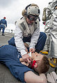 U.S. Navy Hospitalman Kassandra Peters, top, applies bandages to a simulated helicopter crash casualty on the flight deck of the guided missile destroyer USS Ross (DDG 71) in the Atlantic Ocean March 17, 2014 140317-N-WX580-076.jpg