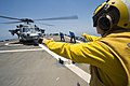 U.S. Navy Lt. j.g. Casey Strouse signals Sailors to remove chocks and chains from an MH-60S Seahawk helicopter attached to Helicopter Sea Combat Squadron (HSC) 9 on the flight deck of the guided missile 140628-N-WD757-114.jpg