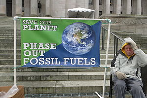 "Energy transition - Protest at the Legislative Building in Olympia, Washington. Ted Nation, activist for several decades, beside sign reading ""Save our planet. Phase out Fossil Fuels"