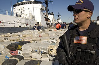 A Coast Guardsman stands guard over more than 40,000 pounds of cocaine worth an estimated $500 million being offloaded from the Cutter Sherman, April 23, 2007. The drugs were seized in three separate busts near Central America. The offload included approximately 38,000 pounds of cocaine seized in the largest cocaine bust in maritime history. USCoastGuardCocaineApr23.07.jpg