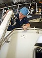 US Navy 020809-N-7871M-001 Boatswain's Mate polishes a mast light on the Captain's Gig in the hangar bay.jpg