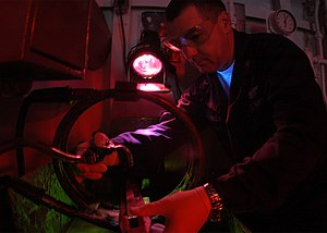 Magnetic particle inspection - Using a similar machine, a U.S. Navy technician sprays magnetic particles on a test part under ultraviolet light.