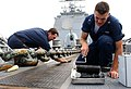 US Navy 040628-N-4143O-001 Boatswain's Mates 3rd Class Dominic Tintari, from Chicago, Ill., and Eric Welker, from Globe, Ariz., assigned to the guided missile cruiser USS Cowpens (CG 63) perform maintenance.jpg