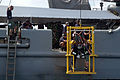 US Navy 060607-N-4205W-006 1st Sgt. Adrian Tay from the Republic of Singapore Navy (RSN) and Machinist's Mate 3rd Class Scott Gee are lowered into the water on the stage from the side of rescue and salvage ship USS Salvor (ARS.jpg