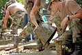US Navy 060811-N-0553R-002 Builder Constructionman Steven Deboard assigned with Naval Mobile Construction Battalion One (NMCB 1) pours concrete into the forms as Builder Constructionman Apprentice Nathaniel Huckins stands by.jpg