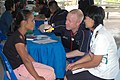 US Navy 070619-N-7783B-003 Cmdr. Warren Woollin, assigned to Operational Health Support Unit Detachment Golf Great Lakes, performs a routine medical exam on a Thai citizen, with the assistance of a Royal Thai Army nurse.jpg