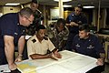 US Navy 080607-G-2443T-001 Coast Guard Capt. Robert Wagner, right, commanding officer of the Coast Guard Cutter USCG Dallas (WHEC 716), and law-enforcement officers discuss tactics during an operational brief aboard the ship.jpg