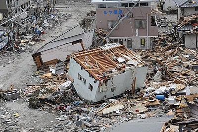 US Navy 110315-N-2653B-107 An upended house is among debris in Ofunato, Japan, following a 9.0 magnitude earthquake and subsequent tsunami.jpg