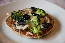 A homemade vegetarian pizza on whole-grain bread with multiple types of vegetables