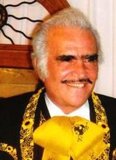An aged man smiling wearing a charro suit.