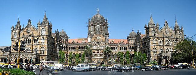 A brown building with clock towers, domes and pyramidal tops. Also a busiest railway station in India.[311] A wide street in front of it