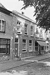 foto van Pand met rechte bepleisterde gevel aan de straat en schilddak. Rechts winkelpui, links woonhuis. Hardstenen stoeppaal met 18e-eeuws ijzer
