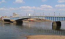 A long low bridge across a wide river. The bridge is painted in varying shades of blue, which render it hard to see against the water and sky.
