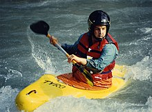 Photo of man in kayak holding paddle nearly parallel to the boat, surrounded by white water