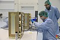 Workers attach a panel for new cubesats in the SSPF.jpg