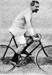 A man posing while sitting on a bike.