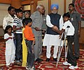 A handicapped child tying 'Rakhi' to the Prime Minister, Dr. Manmohan Singh, on the occasion of 'Raksha Bandhan', in New Delhi on August 05, 2009.jpg