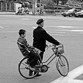 A man is holding cycle with kid.jpg