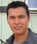 """A colour bust photo of Adam Ruebin Beach wearing a grey leather bomber jacket."""