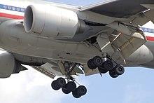 Брюшная часть самолета.  Крупным планом - двигатели, удлиненное шасси и наклонные закрылки.