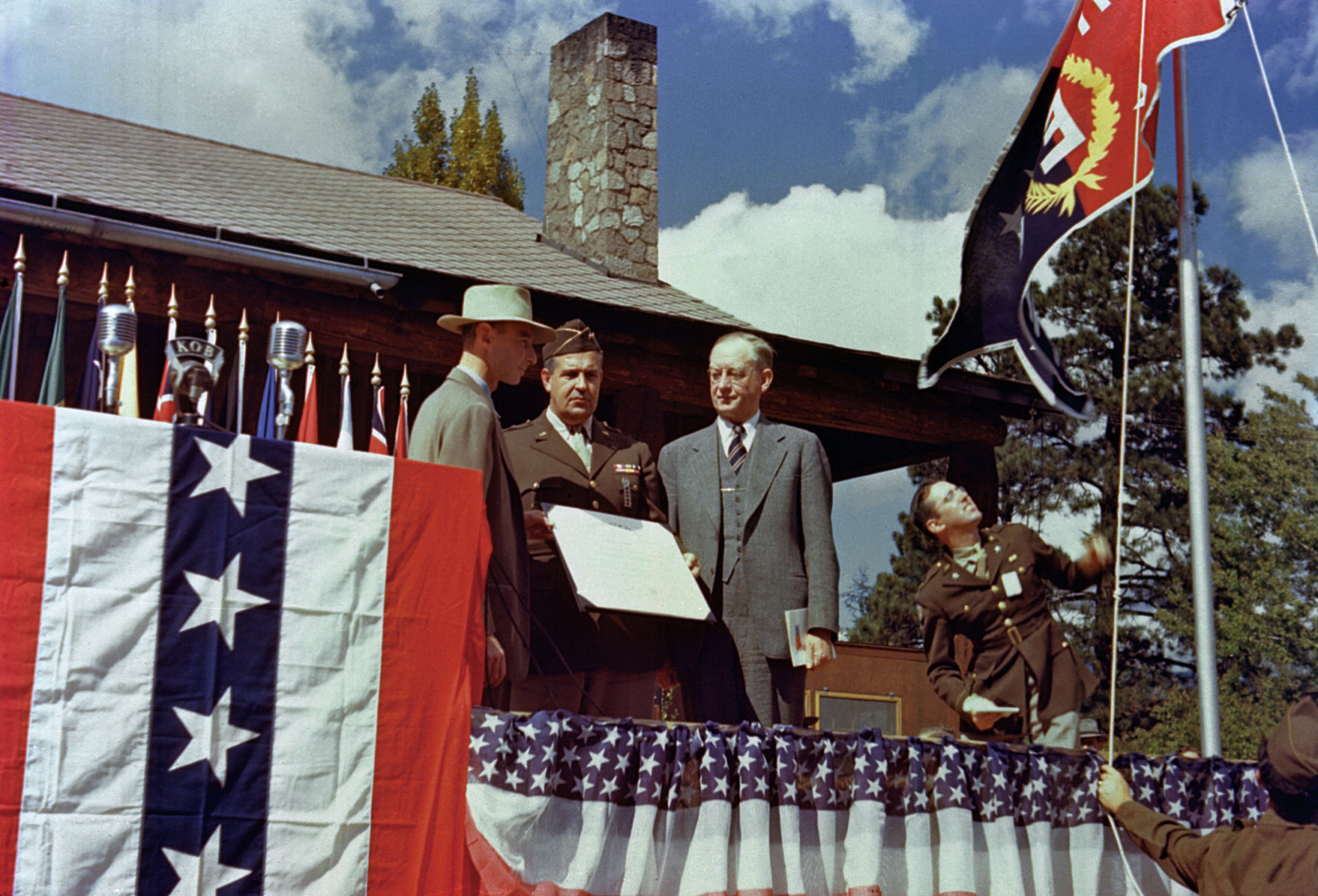 "Presentation of the Army-Navy ""E"" Award at Los Alamos on October 16, 1945. Oppenheimer (left) gave his farewell speech as director on this occasion. Robert Gordon Sproul right, in suit, accepted the award on behalf of the University of California from Leslie Groves (center).[92]"