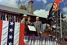 A large house with a stone chimney, decorated with bunting. An army officer runs a red and blue flag up a flagpole. In the foreground are two men in suits and one in an army uniform.