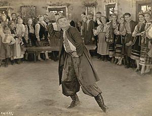 "Vasyl Avramenko - Film still, from ""Natalka Poltavka.""  Vasile Avramenko, in costume, doffs his hat during a dance sequence."