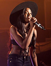 Azealia Banks performing with a microphone in-hand.