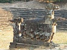 Statuie mare de bloc de piatră a unui cal cu membrele întinse înainte, bărbații agățați de părțile laterale.