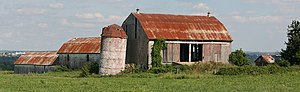 A short silo in the centre of the photograph is slanted slightly to the right, topped by a conical red roof. Three barns form a V shape behind the silo. To its right is a large barn, with slanted red roof and open doors. Perpendicular to it are two similar but smaller barns in series, visible to the left of the silo.