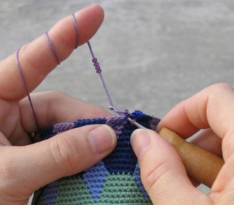 Tapestry crochet - Since the beads fall to the back of the stitches, tapestry crocheted fabric can have beads on one side and colorful motifs on the other. A hook with a handle makes it easier to crochet tight stitches.