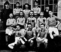 A group of thirteen men, eleven in association football attire typical of the late nineteenth century and two in suits and bowler hats