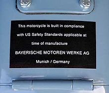 "Black placard mounted on a light blue fuel tank, which reads ""This motorcycle is built in compliance with US safety standards applicable at the time of manufacture BAYERISCHEN MOTOREN WERKE AG Munich / Germany"""