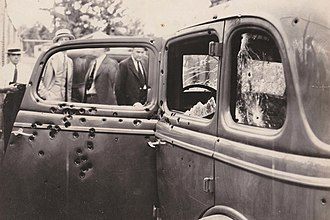 Ted Hinton - The vehicle of Bonnie and Clyde is shown riddled with bullet holes after the ambush. The picture was taken by FBI investigators on May 23, 1934