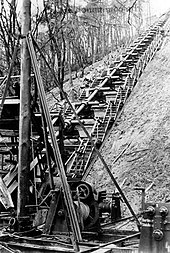 A single Hochdruckpumpe barrel mounted on the side of a steep wooded hill, with flights of steps on each side of it and machinery in the foreground