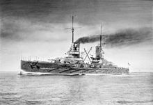 A large warship underway. Dark smoke billows from its smoke stacks.