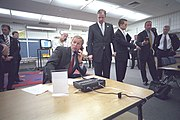 President Bush sits at a table talking on a phone surrounded by advisors