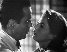 Black-and-white film screenshot of a man and woman as seen from the shoulders up. The two are close to each other as if about to kiss.