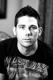 Black and white picture of a man wearing a printed T-shirt and earrings in both earlobes