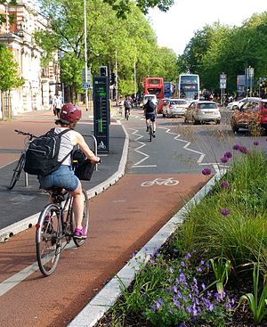 Cycling in Manchester - Cyclists using the cycle lane on Oxford Road, passing an electronic bicycle traffic counter.