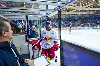 An ice hockey player enters the penalty box. Players may be sent to the penalty box for rule infractions, forcing their team playing with one less player for a specified time. David Meckler enters the penalty box.jpg
