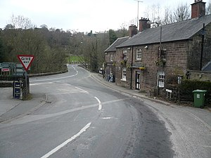 Whatstandwell - The A6 road from the Derby direction at the left behind the road-sign, with first half of the 'S' bend, the bridge over the River Derwent, and the right-turn in the distance where the road proceeds towards Matlock