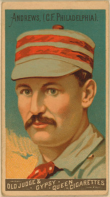 A baseball-card image of a mustachioed man wearing a red-and-white striped pillbox hat