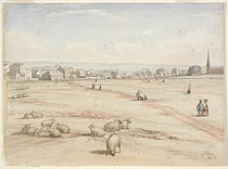 A watercolour showing the church in the distance with several buildings. Sheep are grazing in the foreground.
