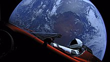 Large circular disc of a fully-illuminated planet Earth showing Australia floating in the blackness of space. In front of Earth is a red convertible sports-car seen from the side. A humanoid figure wearing a white-and-black spacesuit is seated in the driving seat with the right-arm holding the steering wheel, and the left-arm resting on the top of the car door.