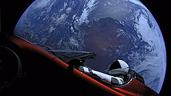 A mannequin (Starman) in a spacesuit drives a car with the Earth in the background