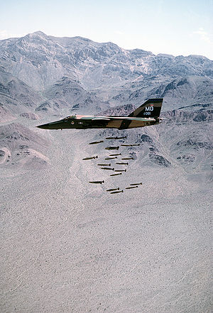 An F-111A dropping 24 Mark 82 low-drag bombs in-flight over a bombing range.