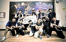 "A group of eleven young men holding a large sign that says ""BBoy Crew Battle Champion"" while posing for a picture in front of a banner that says ""Freestyle Session Taiwan""."