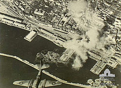 Aerial view of port and plumes of smoke caused by explosions with a bomber in the foreground